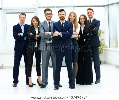 Smiling and confident business team standing in front of a bright window - stock photo