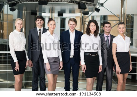 Smiling and confident business team standing in office - stock photo
