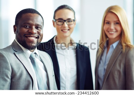 Smiling and confident businessman with two female colleagues on background - stock photo