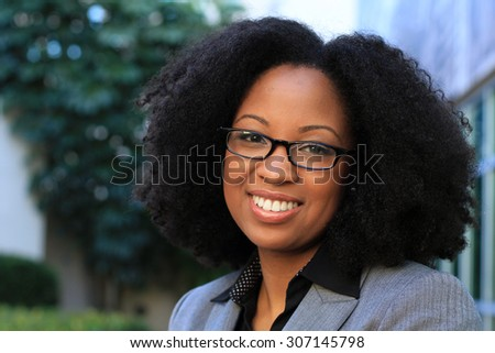 Smiling and Happy Professional African American Business Woman College Student With Black Hair Wearing Glasses - stock photo