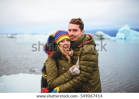 smiling and hugging couple with piece of ice