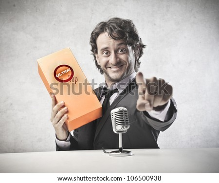 Smiling announcer advertising a product in front of a microphone - stock photo