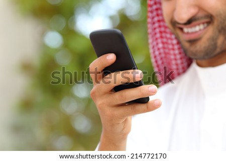 Smiling arab saudi man hand using a smart phone outdoor in a park with a green background - stock photo
