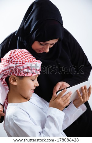Smiling Arabic woman and her son using digital tablet, isolated on white.