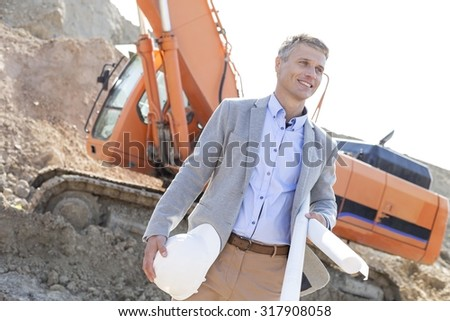 Smiling architect looking away while holding blueprints and hardhat at construction site - stock photo