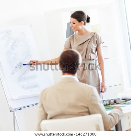 Smiling architect presenting her project to a colleague. - stock photo