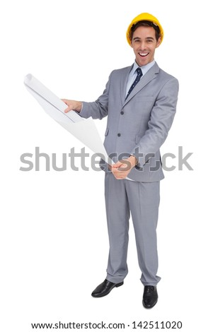 Smiling architect with hard hat holding plans on white background - stock photo
