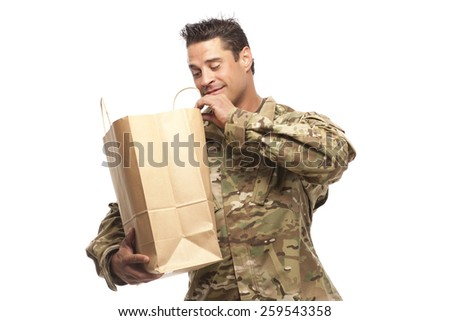 Smiling army soldier looking at his grocery bag in front of white background - stock photo