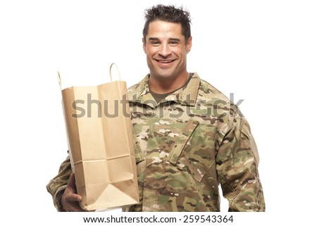 Smiling army soldier with shopping bag in front of white background - stock photo