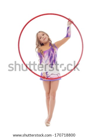 Smiling artistic gymnast posing with red hoop