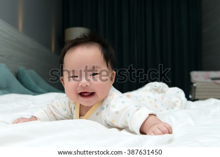 Smiling Asian baby  crawling on white bed