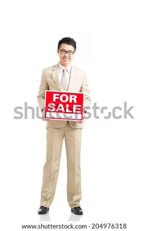 Smiling Asian broker showing for sale signboard - stock photo