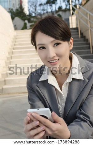 Smiling Asian business woman using cellphone and sit on stairs at outside in modern city.