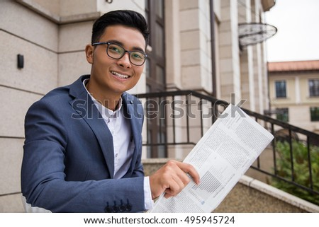 Smiling Asian businessman holding newspaper and smiling to the viewer. Concept of confident man