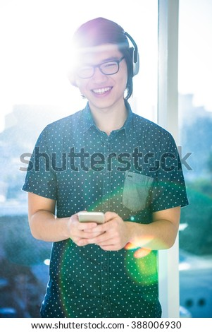 Smiling asian businessman listening to music in office - stock photo