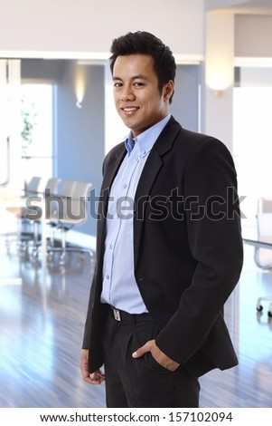 Smiling asian businessman standing at office. - stock photo