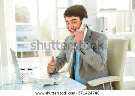 Smiling asian businessman talking on the telephone in his office - stock photo