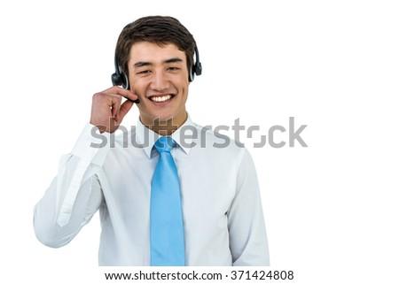 Smiling asian businessman using headset on white screen - stock photo