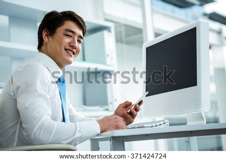 Smiling asian businessman using his telephone in his office - stock photo