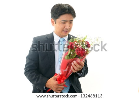 Smiling Asian businessman with flowers