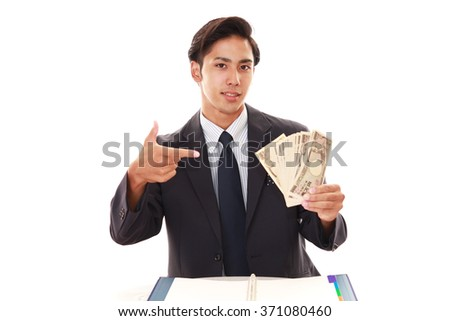 Smiling Asian businessman with money - stock photo