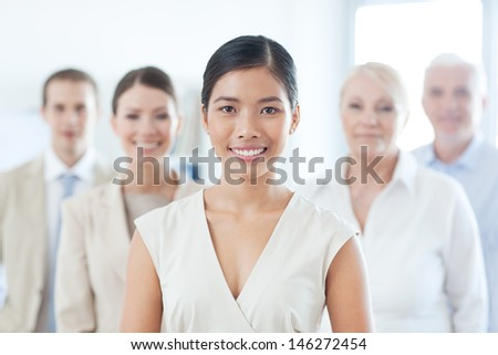 Smiling Asian businesswoman standing in front of her business team.