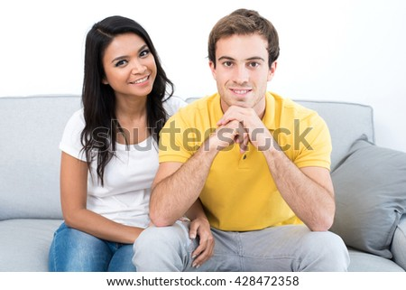Smiling Asian Caucasian couple sitting on the couch in living room