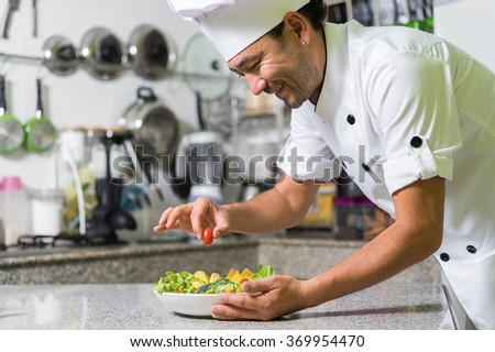 Smiling asian chef put small tomato in vegetarian salad on kitchen background. - stock photo