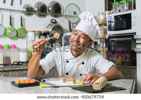 Smiling asian chef showing her  roll  with kitchen background. Focus on the face - stock photo
