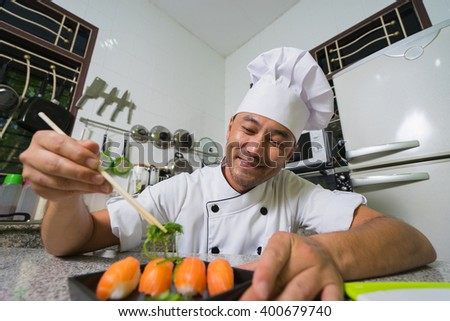 Smiling asian chef showing her sushi on plate with kitchen background. Focus on the face - stock photo