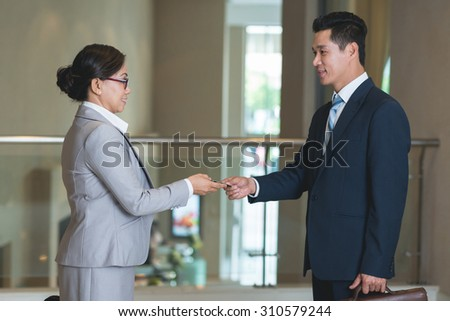 Smiling Asian colleagues exchanging business contacts - stock photo