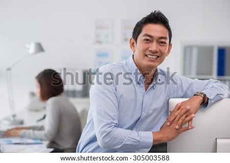 Smiling Asian entrepreneur leaning on the computer monitor and looking at the camera - stock photo