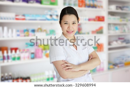 smiling asian female pharmacist with pharmacy drugstore shelves background