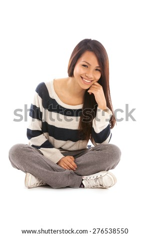 Smiling asian girl sitting on the floor over white isolated background - stock photo