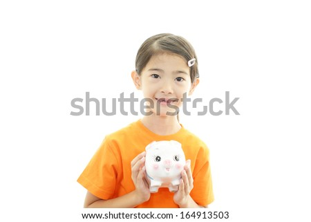 Smiling Asian girl with piggy bank
