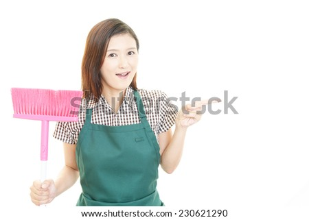 Smiling Asian housewife with a broom