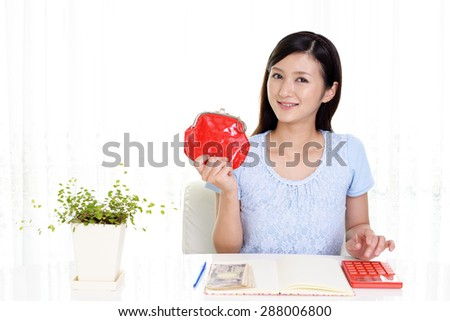 Smiling Asian housewife with money and calculator - stock photo