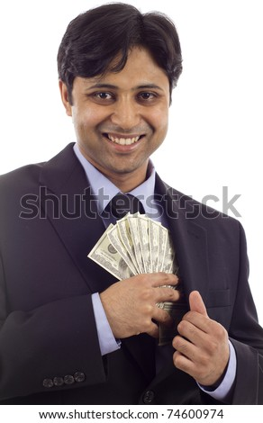 Smiling Asian - Indian businessman in a black suit putting money in his pocket isolated over white background - stock photo
