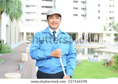 Smiling Asian janitor - stock photo