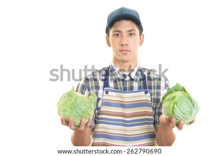 Smiling Asian man with vegetables - stock photo