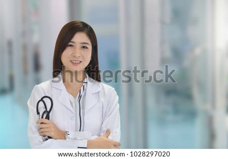 Smiling Asian medical doctor woman with stethoscope in hospital with copy space