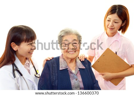 Smiling Asian medical staff and senior woman - stock photo