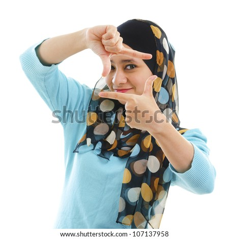 Smiling Asian Muslim woman making a frame with fingers - stock photo