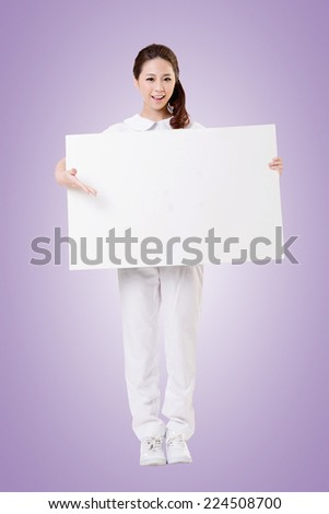 Smiling Asian nurse holding blank board, woman portrait isolated.