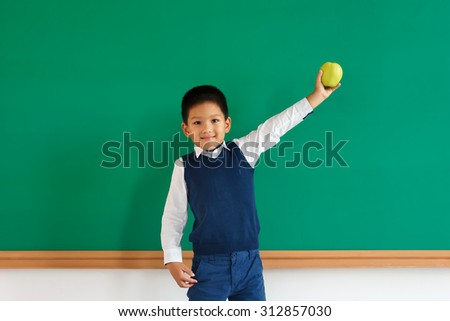 Smiling asian pupil holding green apple / photo of teen school Chinese boy, creative concept with Back to school theme