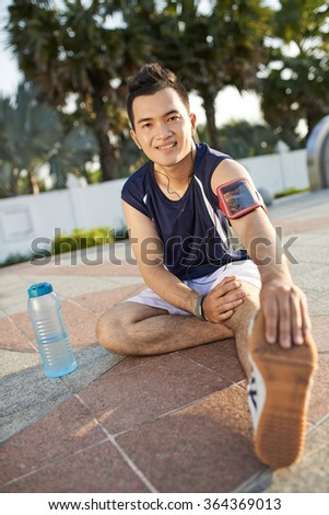 Smiling Asian runner stretching legs after training