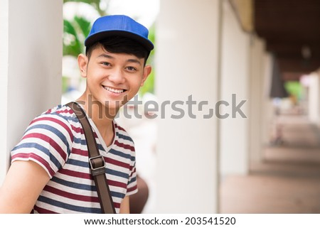 Smiling Asian student in the University building - stock photo