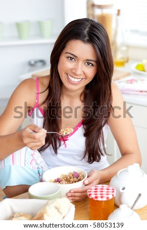 Smiling asian woman eating muesli with fruits sitting in the kitchen - stock photo