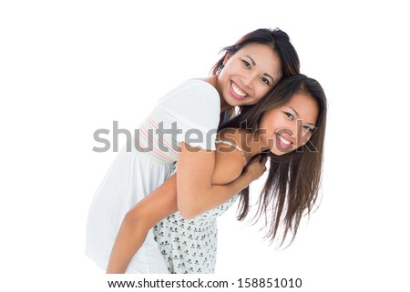 Smiling asian woman giving her sister a piggyback ride on white background - stock photo