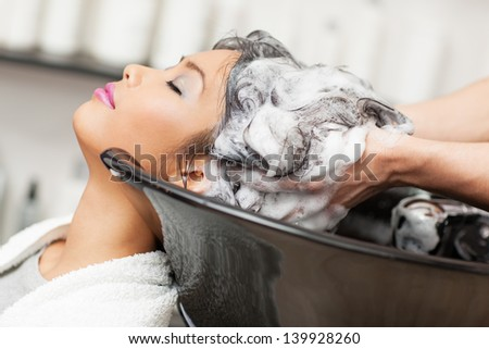 Smiling Asian woman having her hair washed at the hairdresser's. - stock photo
